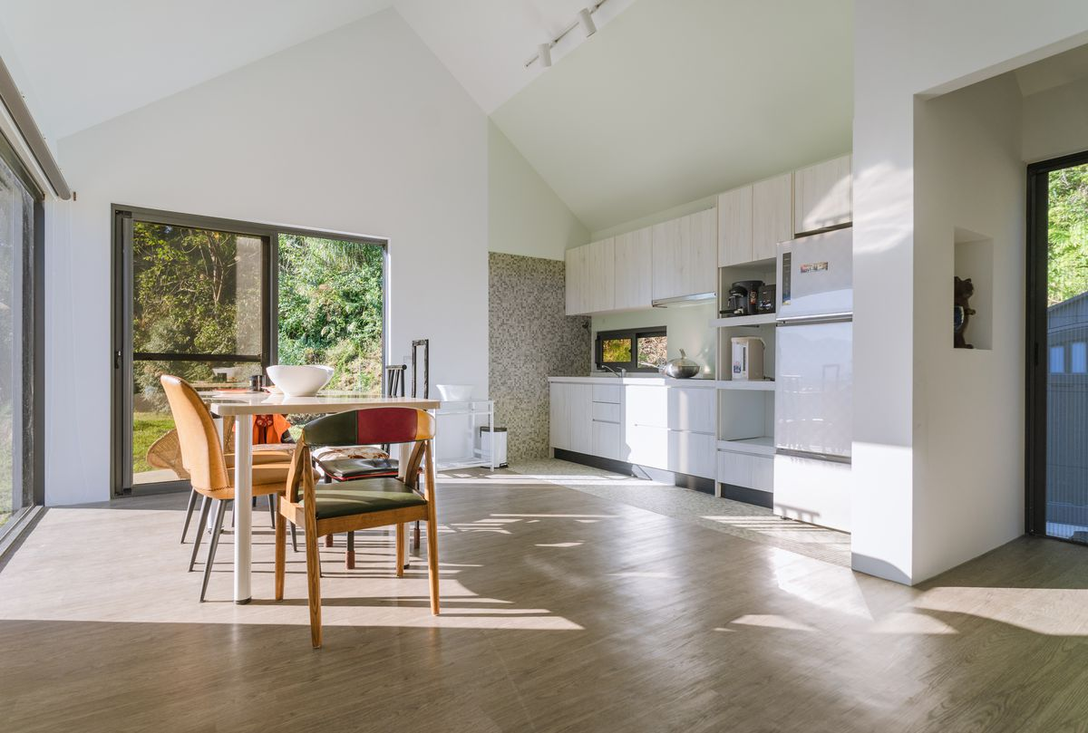 Open kitchen and dining area with white walls and cabinets and large sliding glass doors.