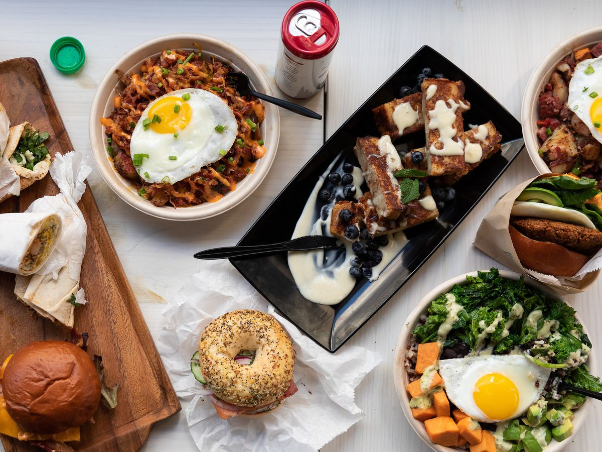 an assortment of sandwiches, bagels, breakfast bowls with fried eggs on top, and French toast