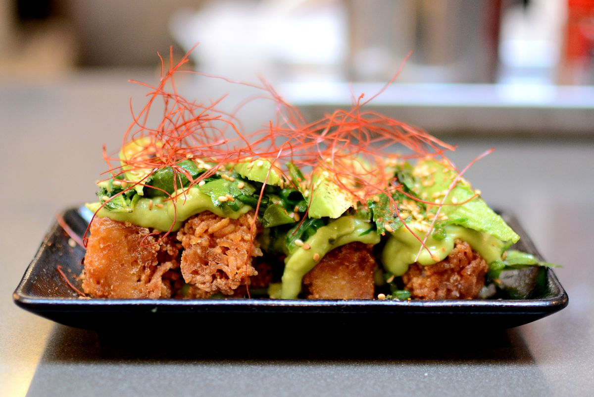 A black plate with crispy rice blocks topped with avocado at Ramen Hood.