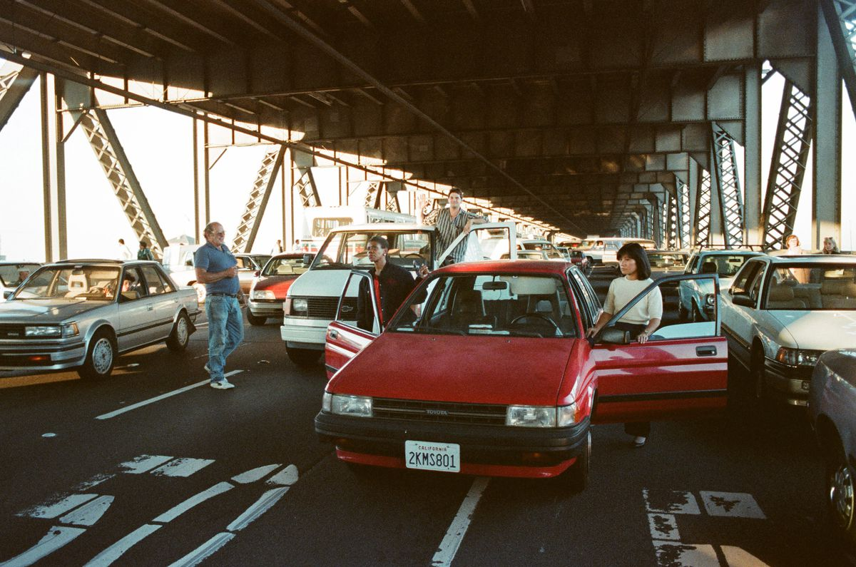 A woman stands outside of her red car while she and other drivers wait on the lower half of the bay bridge.