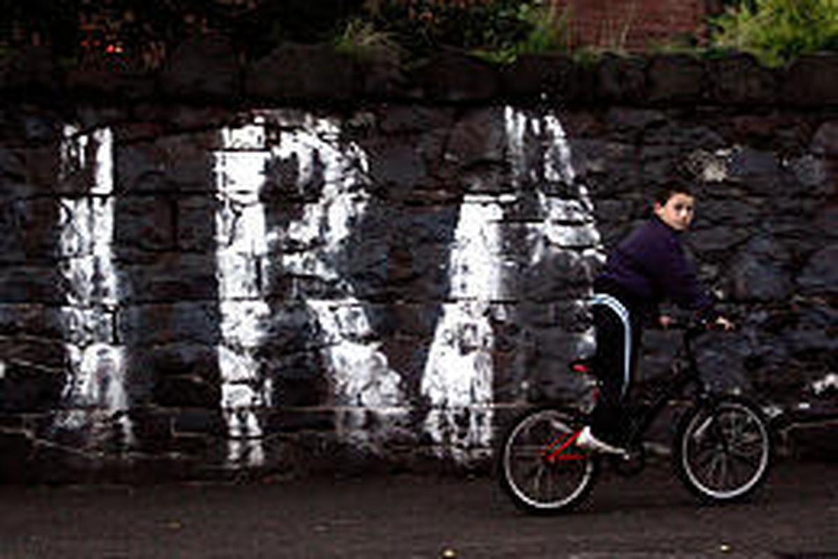 A boy rides by graffiti promoting the long outlawed Irish Republican Army in Belfast, Northern Ireland, Sunday.