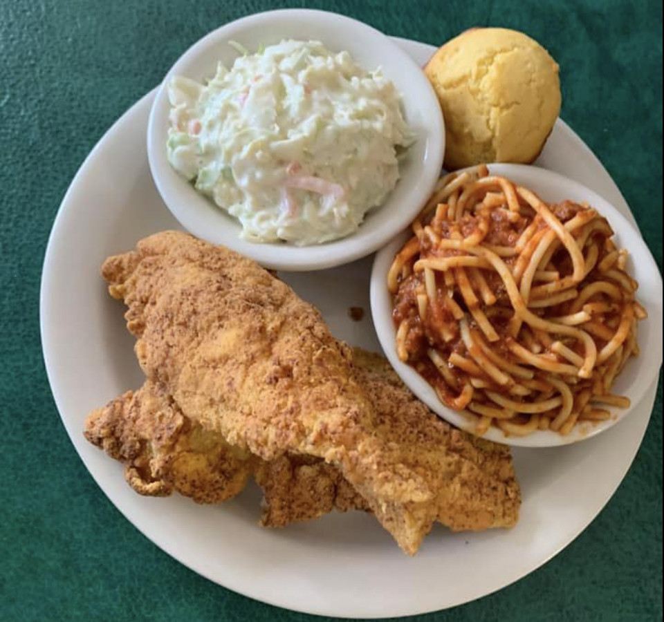 Fried chicken legs share a plate with spaghetti and potato salad.