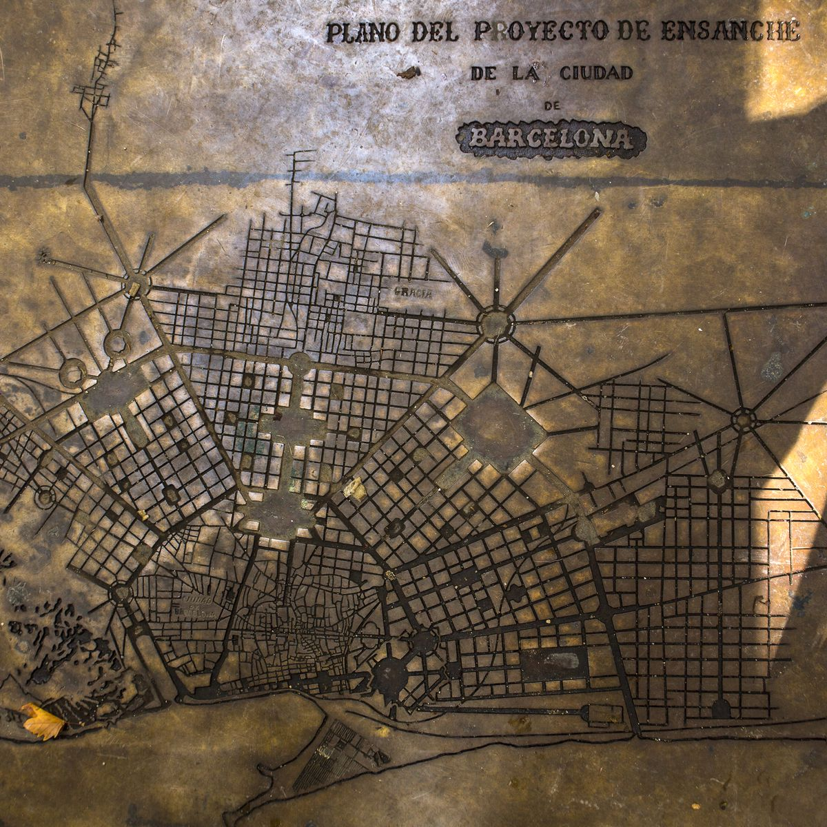 Embedded in the pavement of a plaza in in the Gracia neighborhood superblock: a 19th-century plan for Barcelona that never came to pass. Taken October 14th, 2018. Barcelona, Catalonia, Spain.