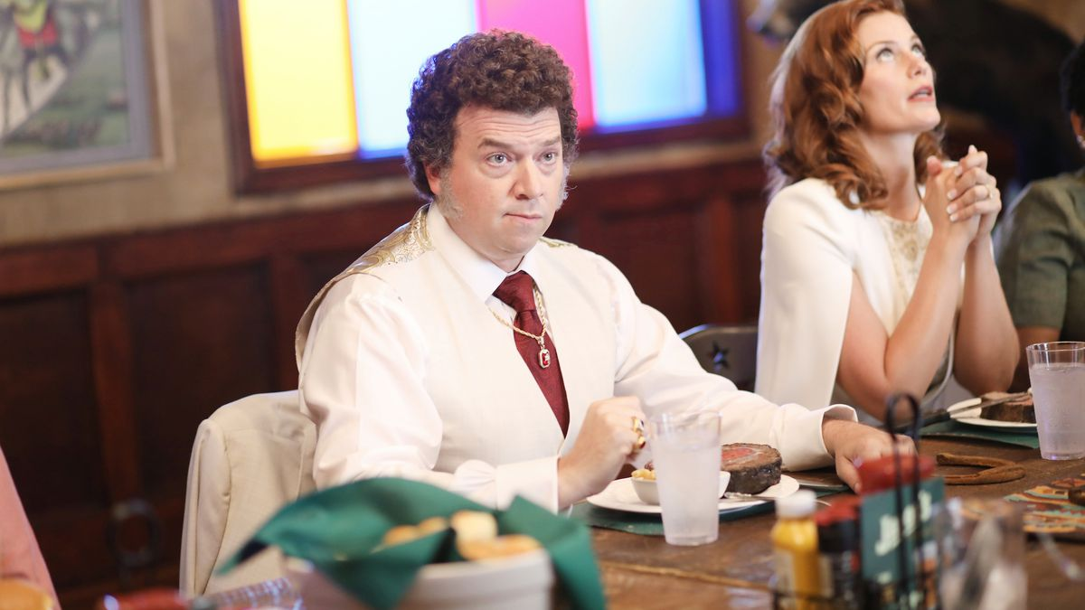 Jesse Gemstone (Danny McBride) commands a board room table as a woman prays to God next to him