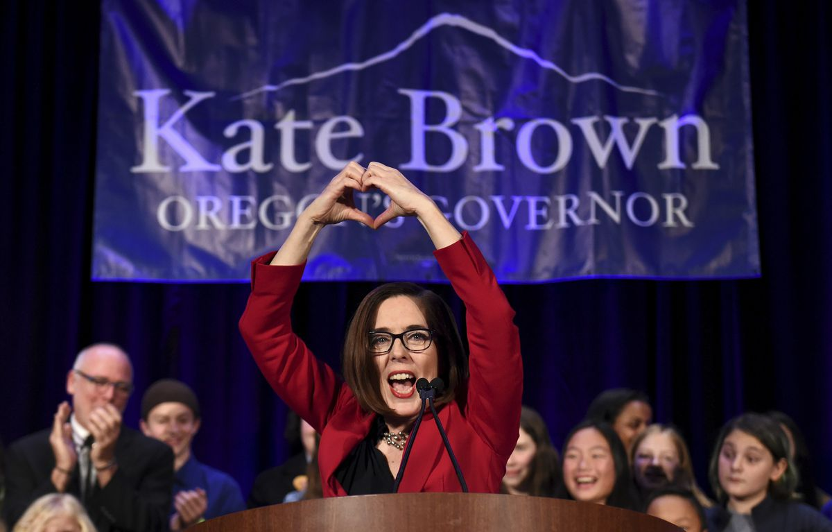 Gov. Kate Brown makes a heart-shape with her hands as she addresses the crowd after winning re-election in Portland, Ore., Tuesday, Nov. 6, 2018.