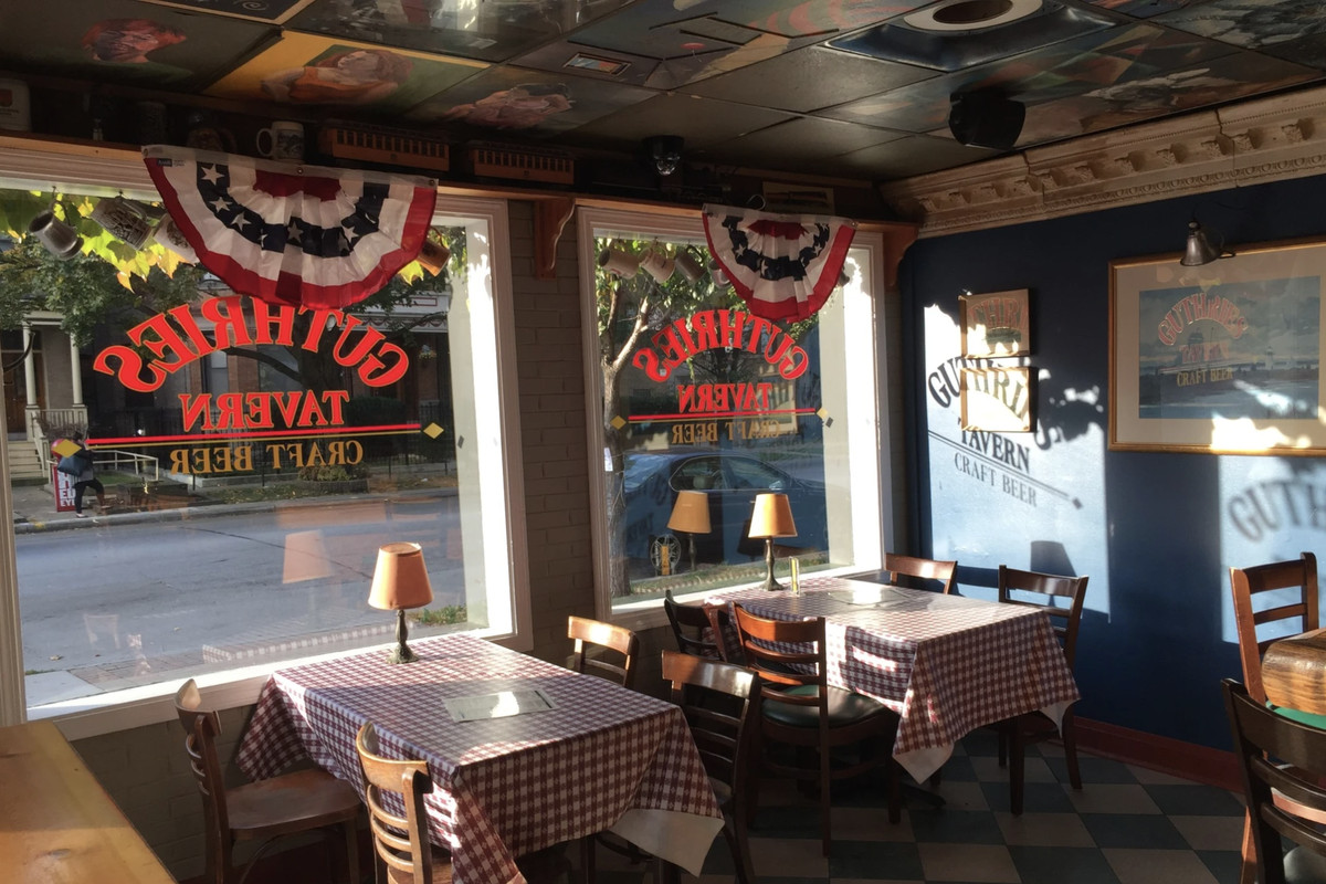The interior of a cozy neighborhood bar with tables with red-and-white checkered tablecloths.