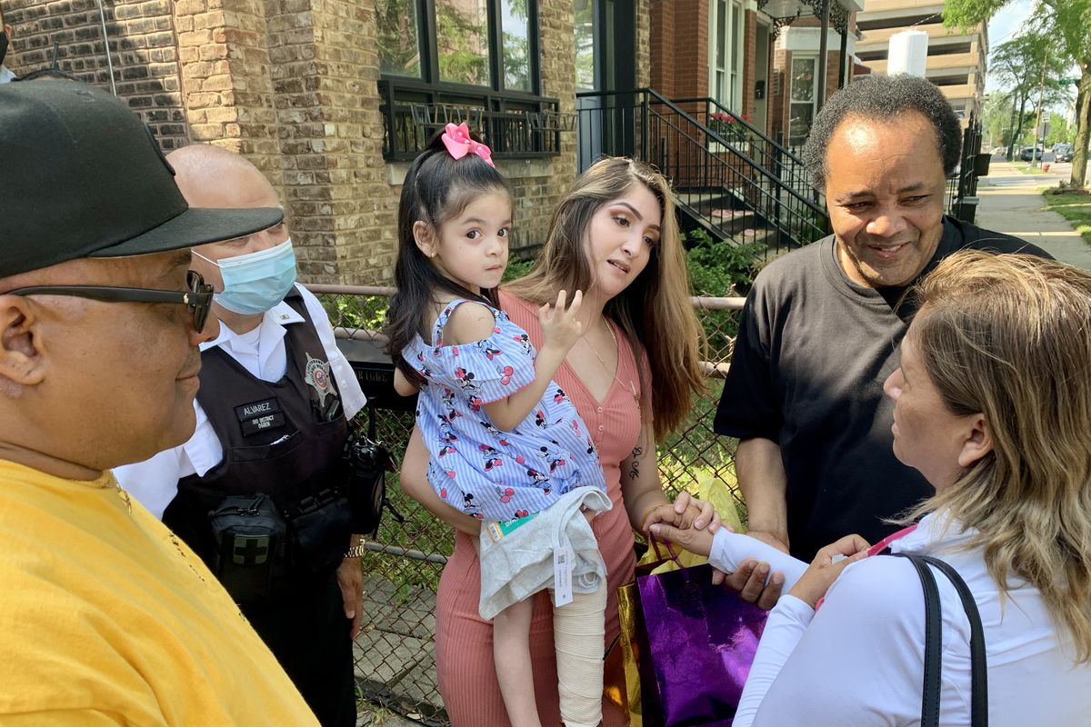 Angelina Rodriguez is held by her mother Perla Rodriguez Saturday outside their West Side home.