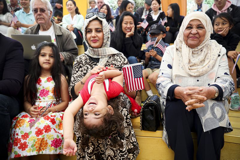 Sabreen Alabdalah (center) and her daughters take part in a children's citizenship ceremony.
