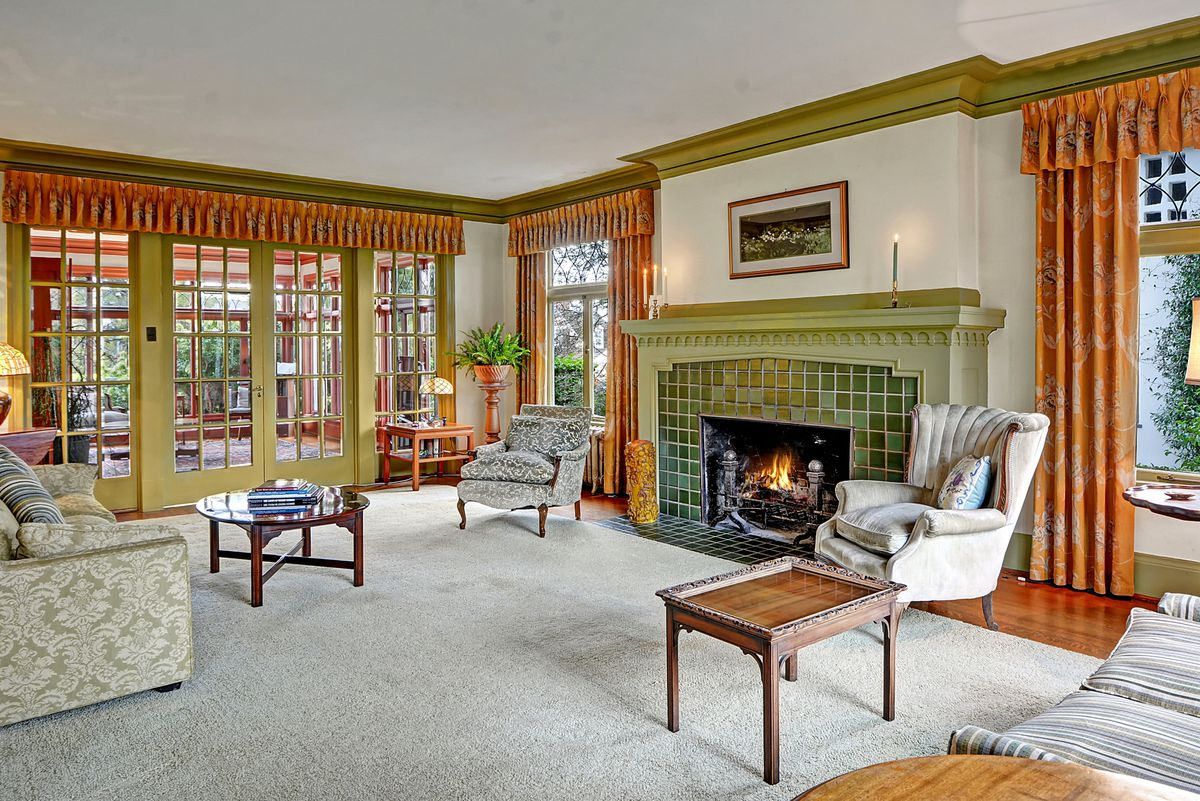 A large living room with a green tile fireplace with green mantle. French doors lead to another room behind it.