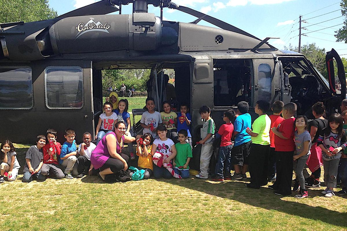 """Valerie Lovato, a first grade teacher at Denver's Eagleton Elementary, poses with her students in front of a military helicopter that landed on the school's soccer field as part of the """"Live Drug Free!"""" initiative."""