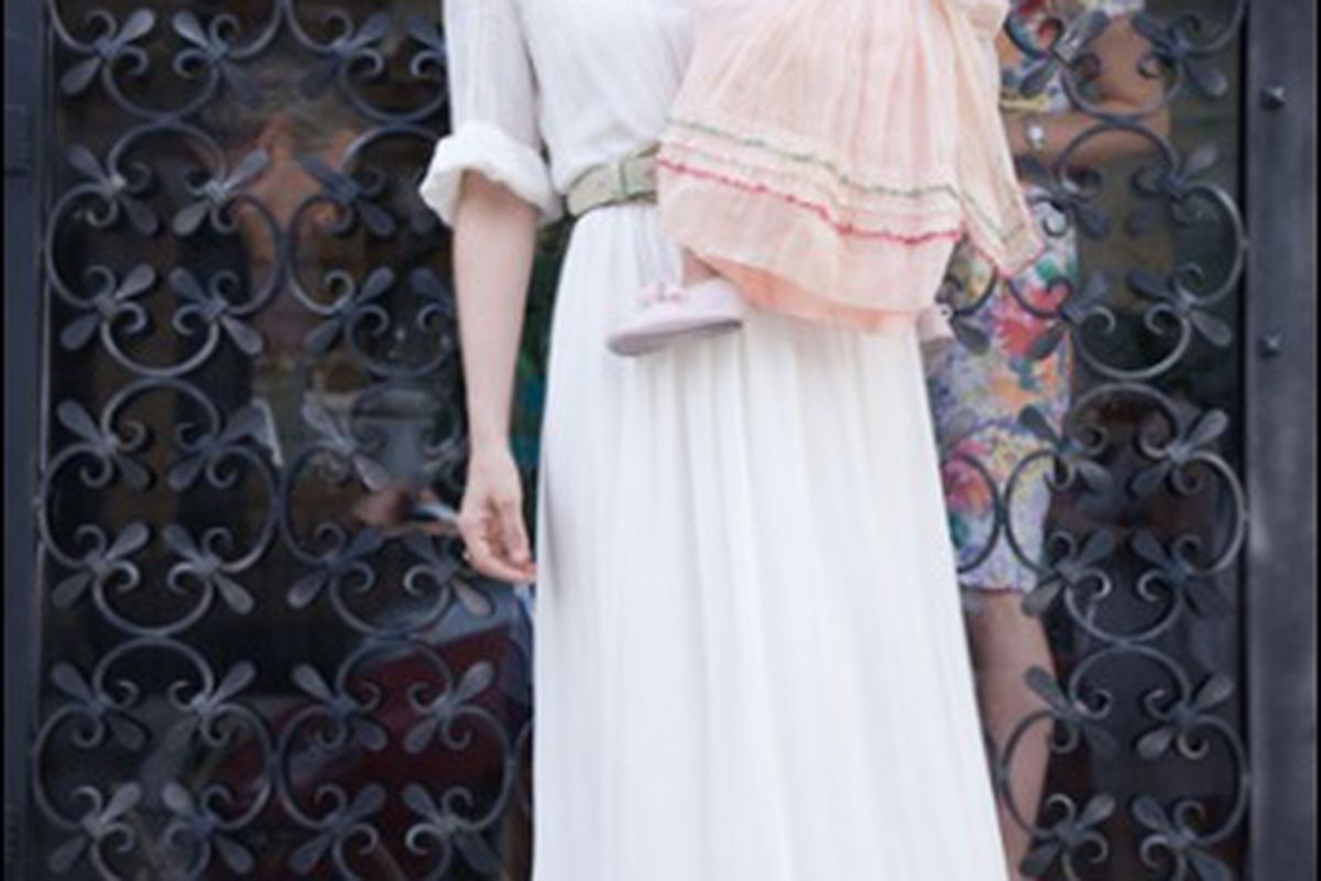 Lauren Moffatt in a wedding dress of her own design holding the cutest flower girl on the planet