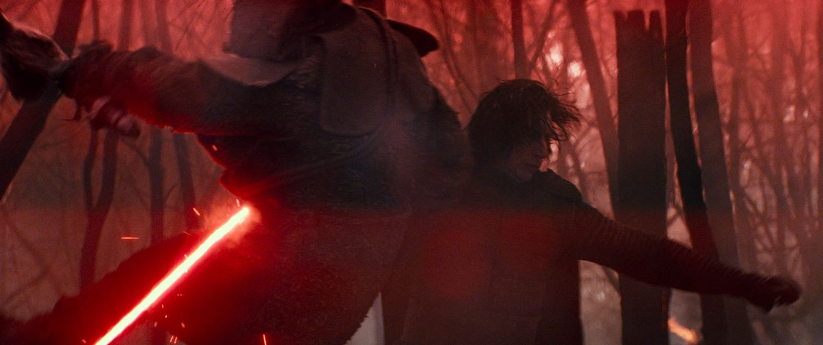 Kylo Ren and his lightsaber tackling an enemy in a forest in Star Wars: The Rise of Skywalker