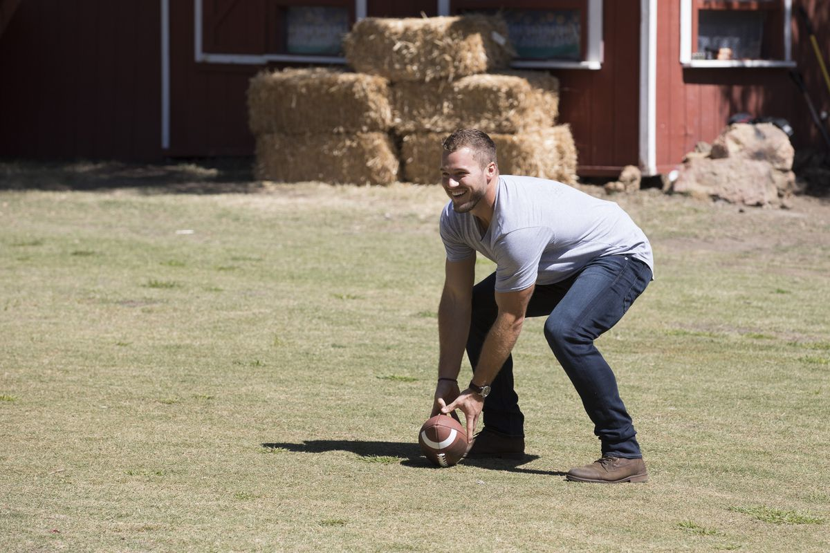 Colton bending down to grab a football