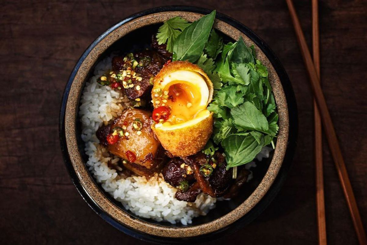 Bowl with rice, greens, meat, and fried egg split open with yolk spilling out