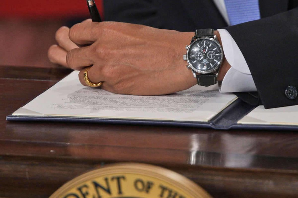 In this Jan. 21, 2009, file photo President Barack Obama signs one of five executive orders his first day on the job.