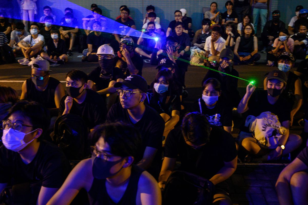 Protesters, some wearing masks, point lasers at a demonstration in Hong Kong in August 2019.