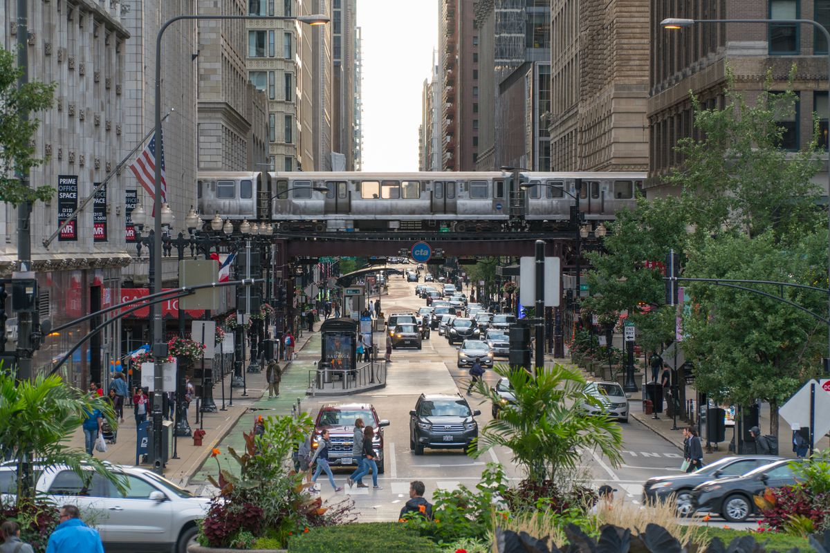 A train on elevated tracks crossing a downtown street between tall towers and buildings.