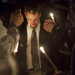 Josh Powell, the husband of Susan Powell, stands with supporters after a candle light vigil for his wife at the Church of Jesus Christ of Latter-day Saints in Puyallup, Wash., Sunday Dec. 20, 2009.