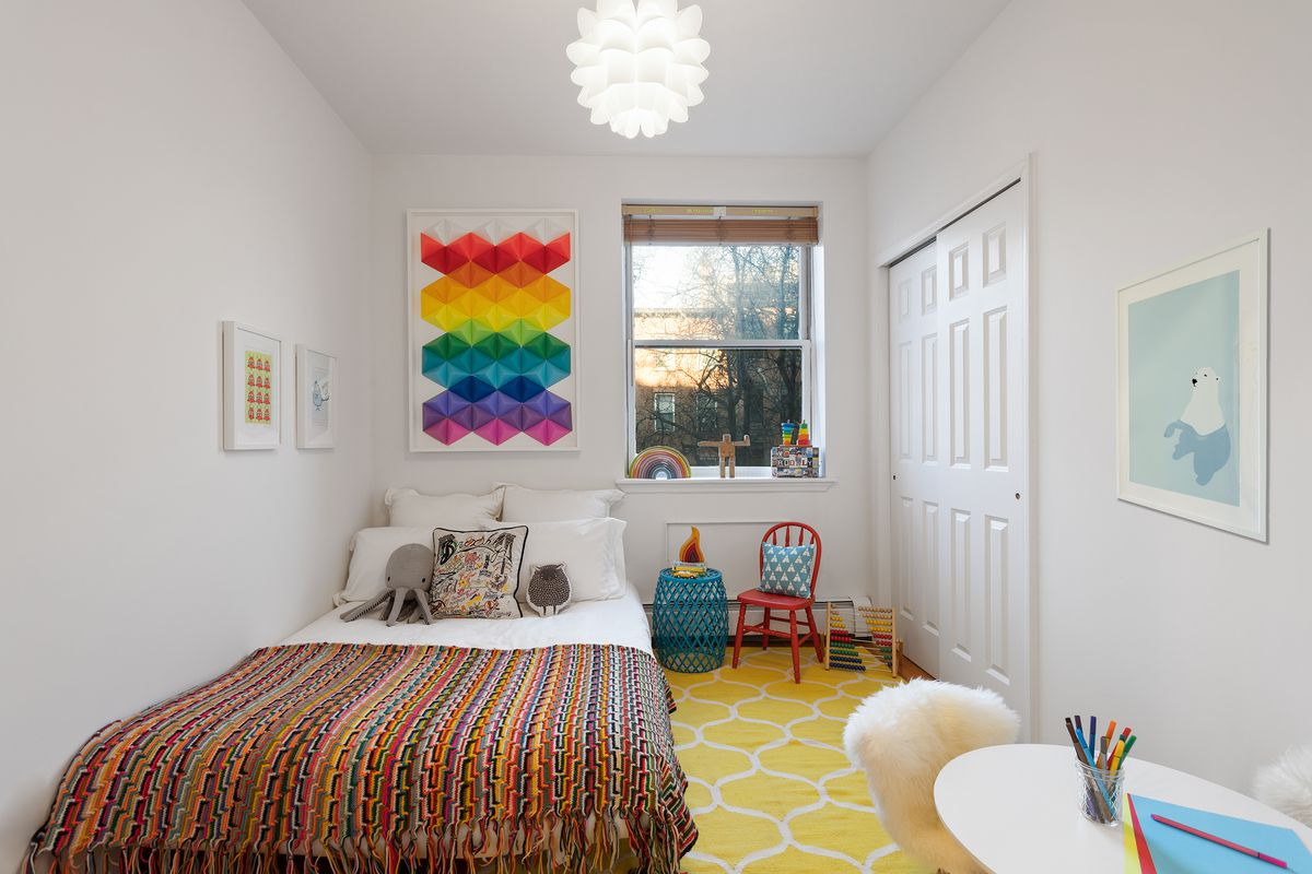 A bedroom with a small bed, a white and yellow rug, a small window, and a small red chair.