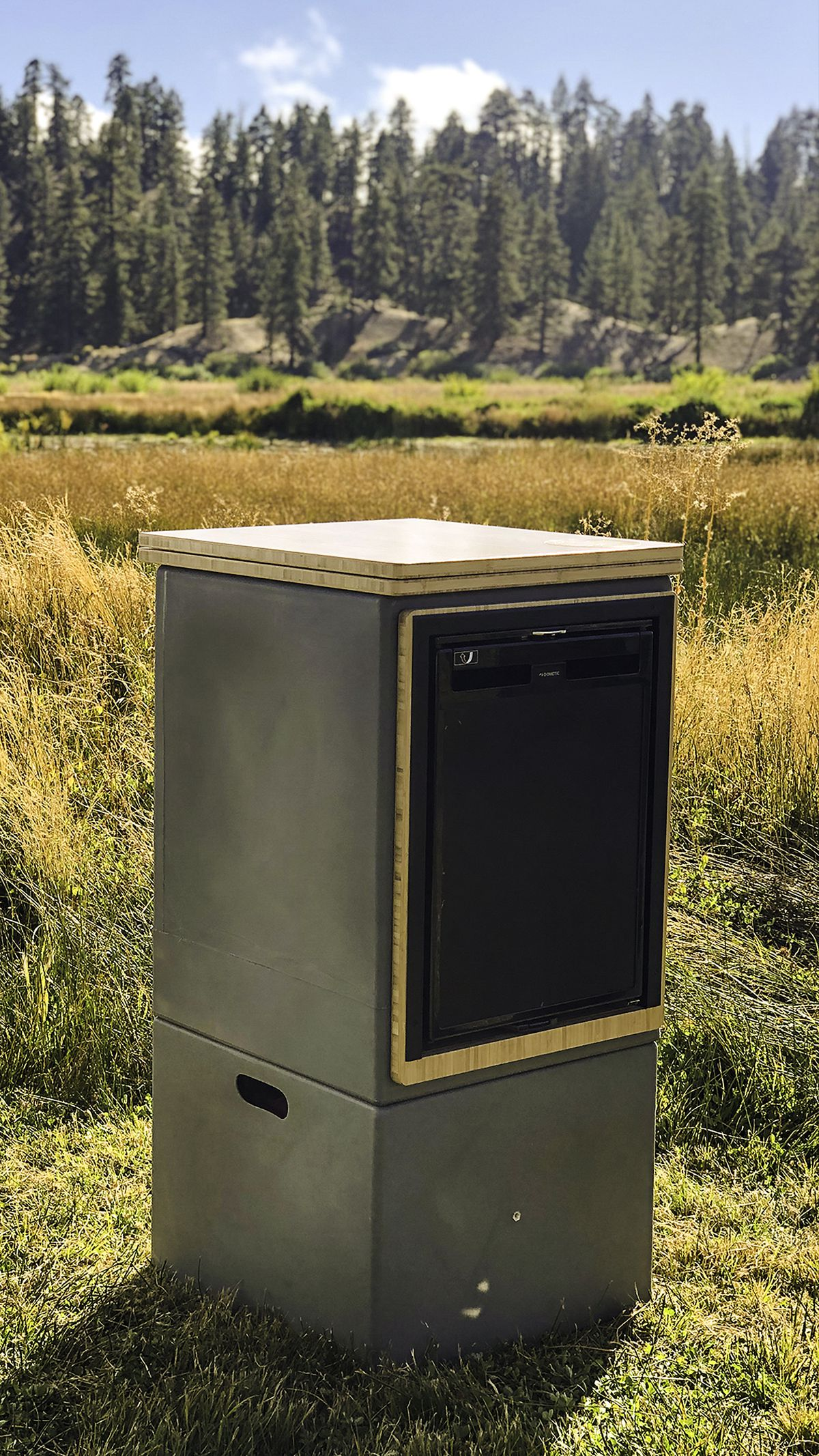A countertop height cube sits in a field. The box features a kitchen countertop and a refrigerator.