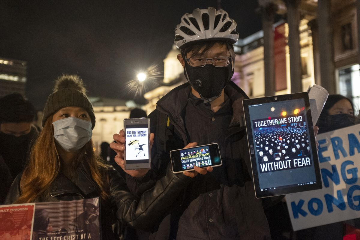 Man and woman in face masks holding phones and a tablet are protesting against the implementation of new laws by the Hong Kong government that forbid protesters from wearing masks in a public protest.