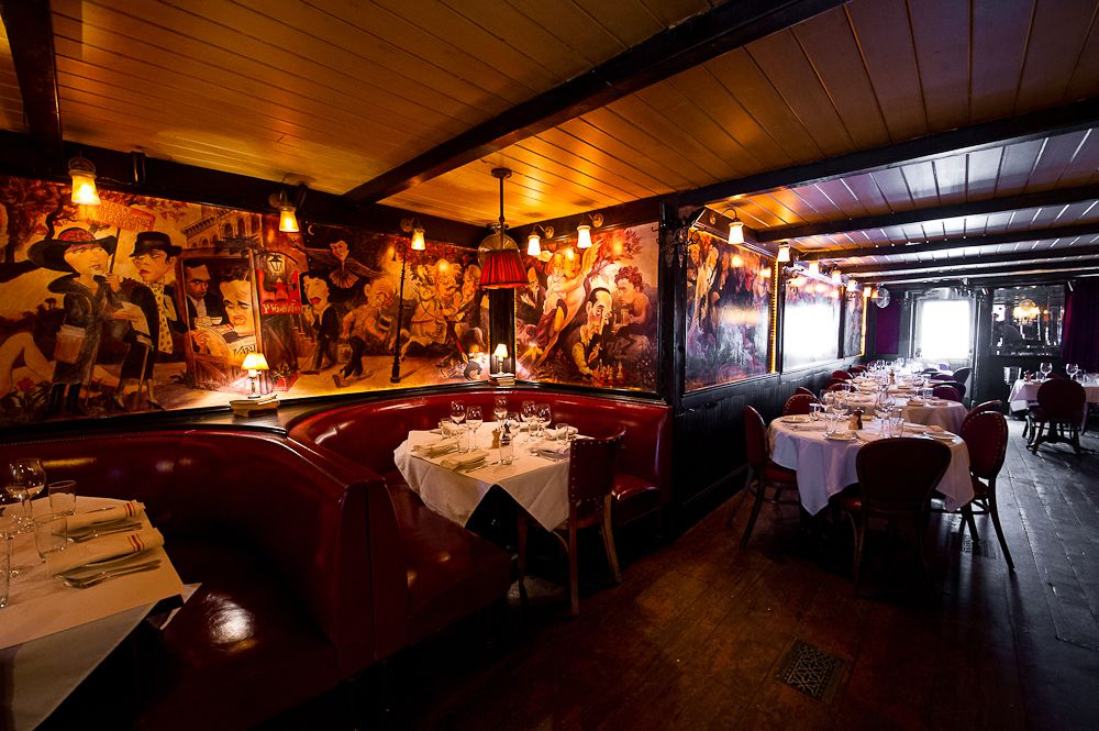 Waverly Inn has a dark dining room with paintingson the walls.