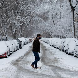 A person crosses the street in Edgewater, Tuesday morning, Jan. 26, 2021. Three inches of snow enveloped Chicago as the winter storm passed through northern Illinois.