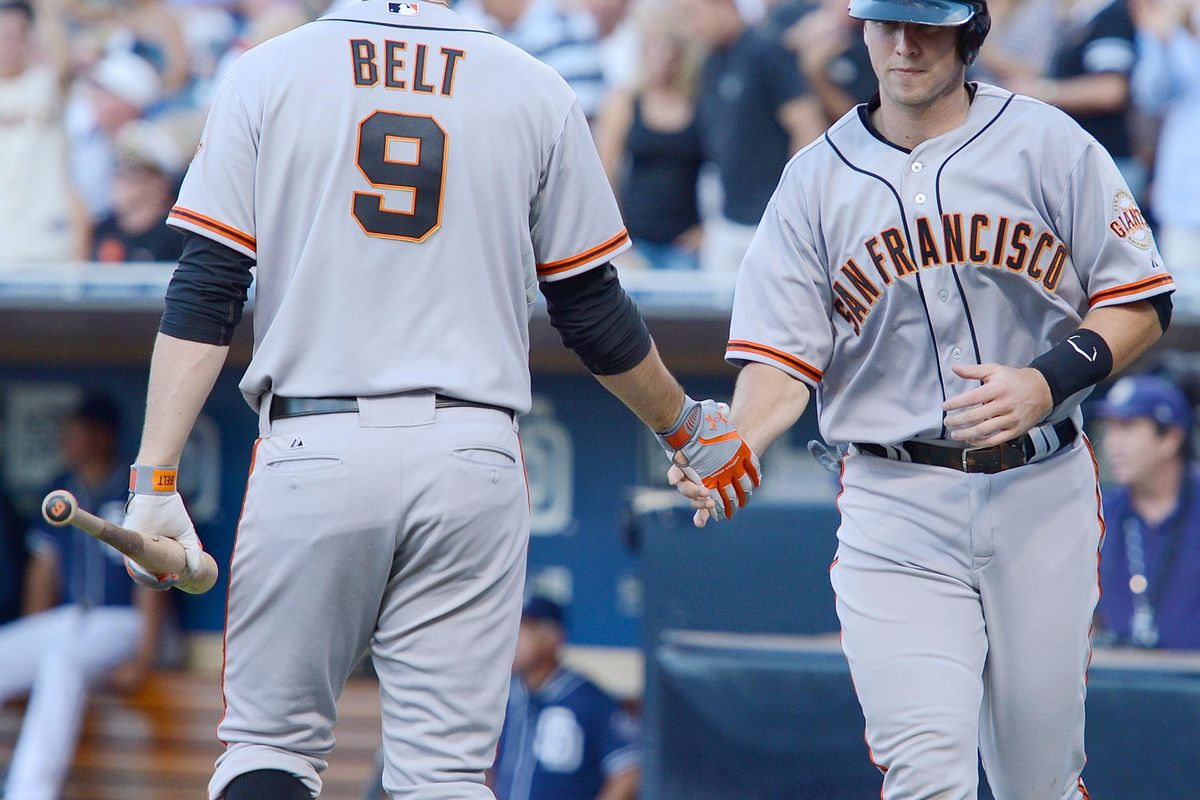 Aug 18, 2012; San Diego, CA, USA; San Francisco Giants catcher Buster Posey (right) provides arms to Brandon Belt. NOT PICTURED: a joke about a pocket zito. Mandatory Credit: Jake Roth-US PRESSWIRE