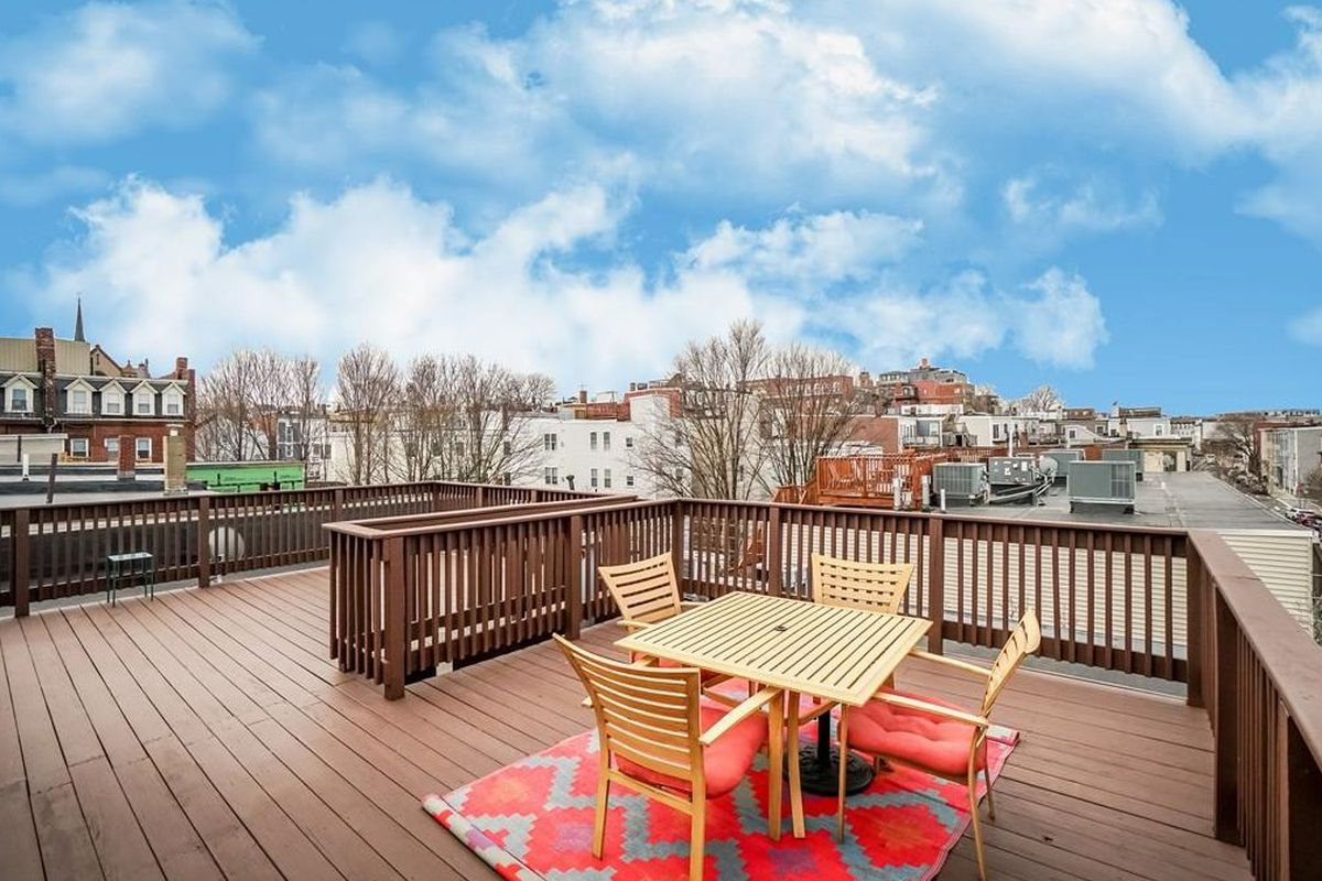 A roof deck atop a short condo building, with city views.