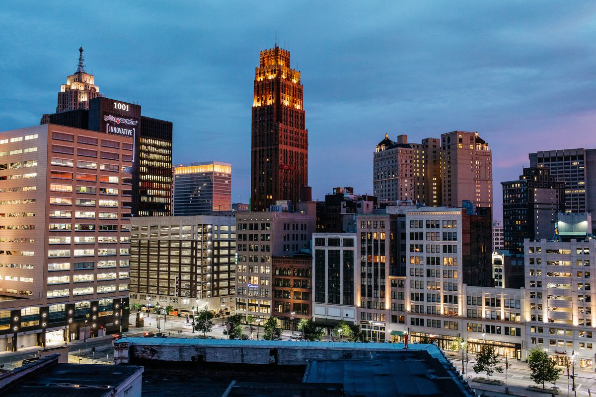 The Detroit skyline shown at dusk with all the building lights on.