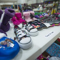 Shoes for young children wait on shelves as the 19th annual Candy Cane Corner holiday store prepares to open in the old Granite High School pool building in South Salt Lake on Monday, Nov. 30, 2015.