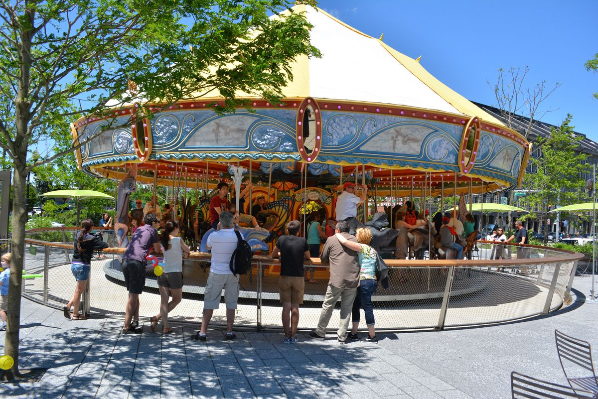 A children's carousel. There are people standing at a fence surrounding the carousel. There are trees in the background.