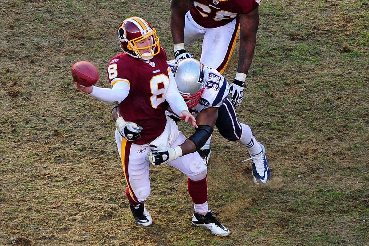 LANDOVER, MD - DECEMBER 11: Rex Grossman #8 of the Washington Redskins passes as he is hit by Andre Carter #93 of the New England Patriots at FedEx Field on December 11, 2011 in Landover, Maryland. (Photo by Scott Cunningham/Getty Images)