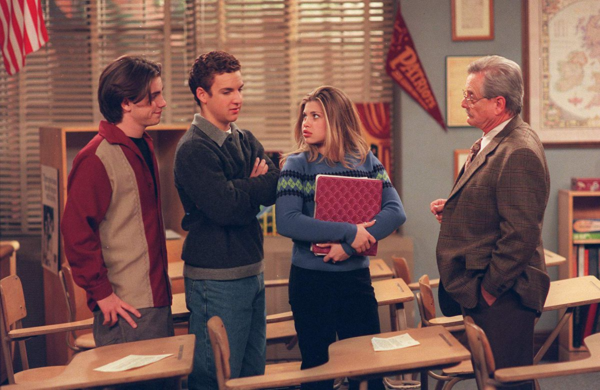 Sean (Rider Strong), Cory (Ben Savage), Topanga (Danielle Fishel), and Mr Feeney (William Daniels) stand in Mr Feeney's classroom