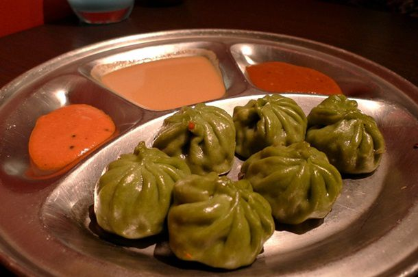 A metal plate of spinach momo dumplings with a variety of chutney sauces.