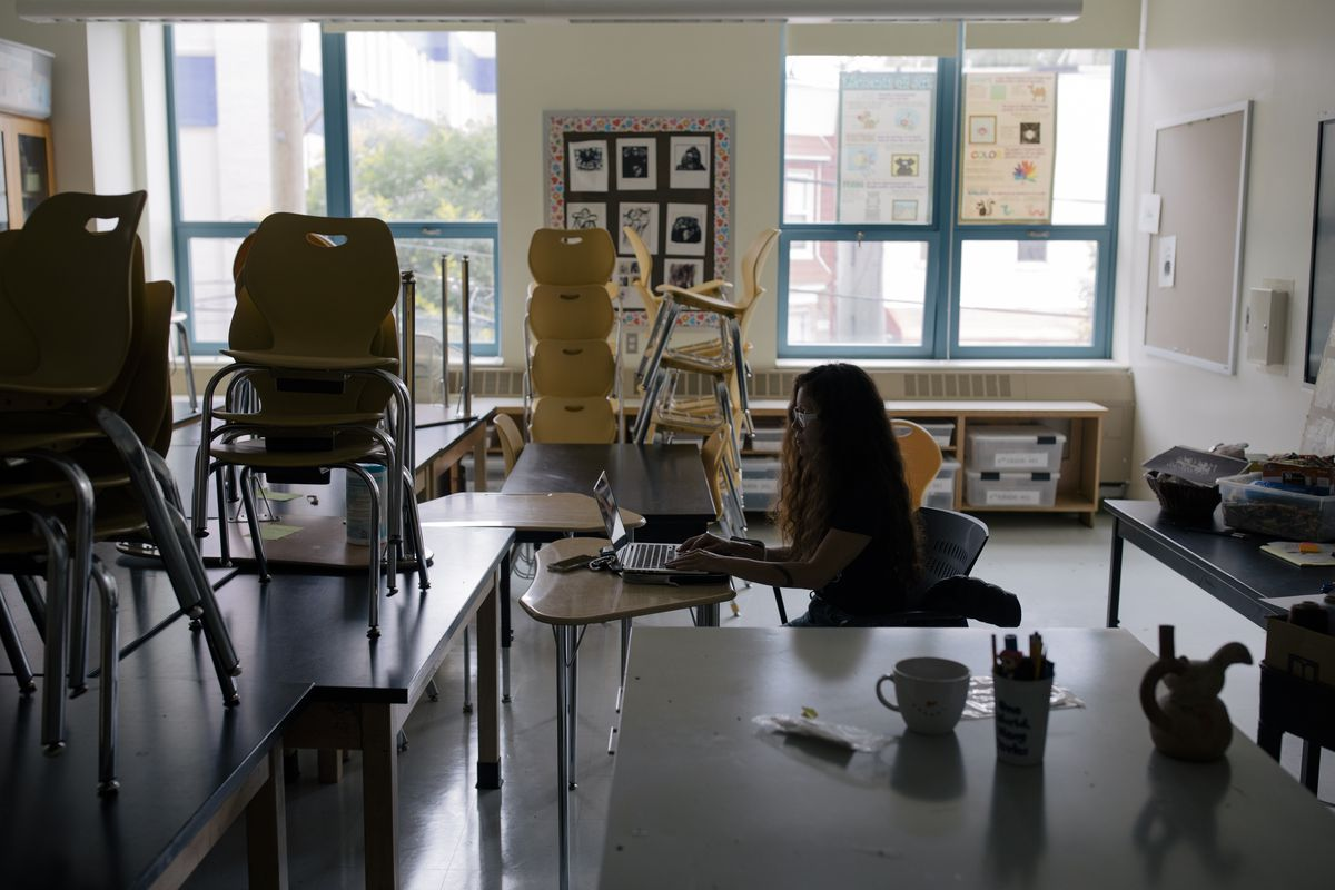 Art teacher Elizabeth Velasquez begins a Zoom class in her empty classroom. The chairs are stacked neatly on desks as she sits at a small desk in the front of the dark classroom.