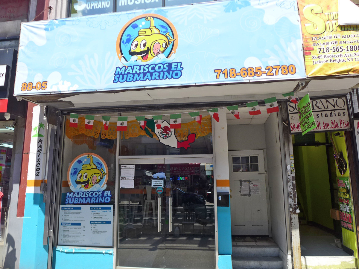 """The exterior of a restaurant in New York City, emblazoned with the words """"Mariscos El Submarino"""" and anthropomorphized yellow submarine with a mustache"""