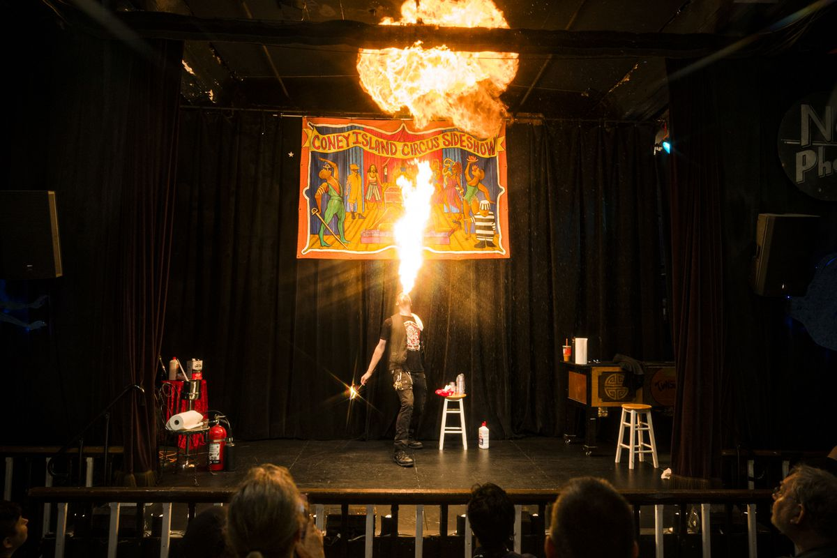 A performer onstage spouts flames from his mouth.