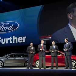 """With two new Ford Mondeo models seen in the background, Raj Nair, group vice President global product development, left, Alan Mulally, President and CEO of Ford Motor Company, center, Stephen Odel, chairman and CEO Ford Europe, and Jim Farley, group vice President global marketing, sales & service, from left to right, answer questions during a presentation of fresh Ford models in Amsterdam, Netherlands, Thursday Sept. 6, 2012. Ford has unveiled 15 new or restyled vehicles for the European market that it will launch over five years to revive sales. The refreshed lineup announced Thursday includes a second-generation Kuga midsize SUV to be launched this year, as well as a new Ecosport compact SUV and the European launch of the larger Edge. Ford also will launch the iconic Mustang in Europe. Ford Europe CEO Stephen Odell said improvements in the """"brutal"""" European market are not expected soon. Ford, he said, is increasing its investment in Europe to be ready when the market bounces back."""