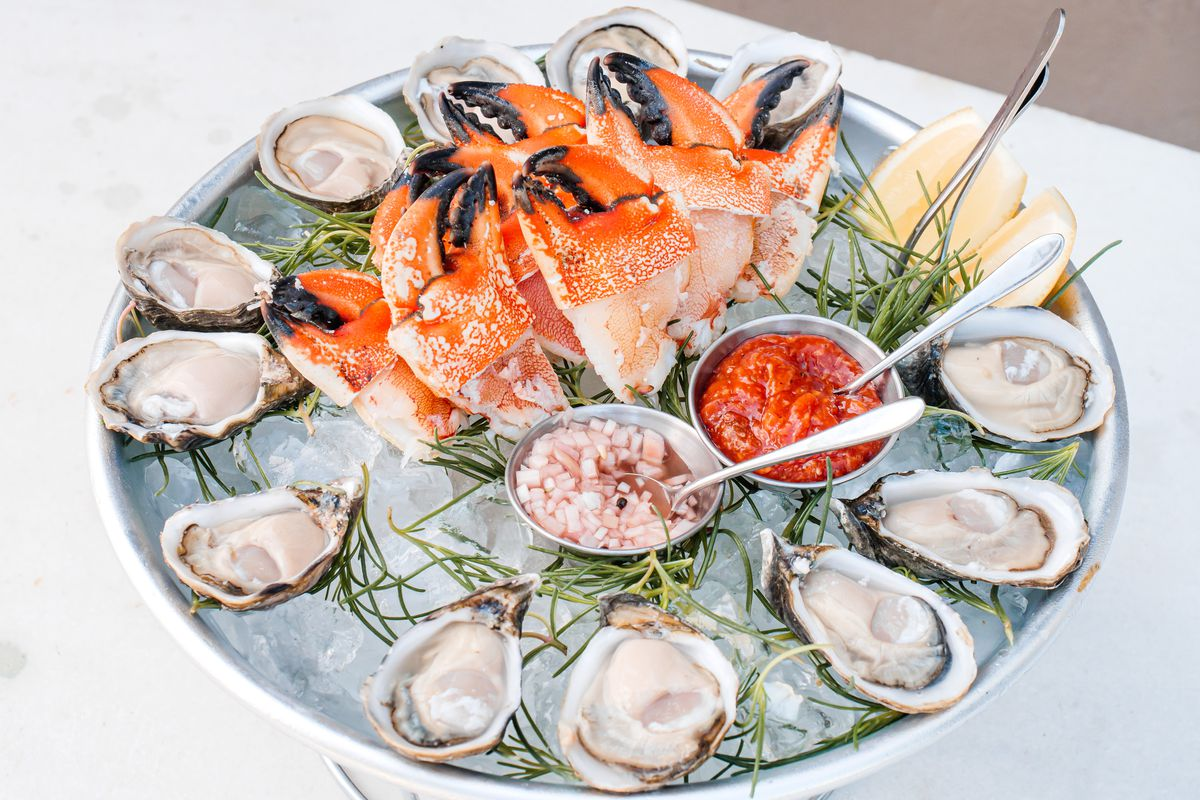 An angled photo of a seafood dish on a stand, with shucked oysters and stone crab and lots of ice.
