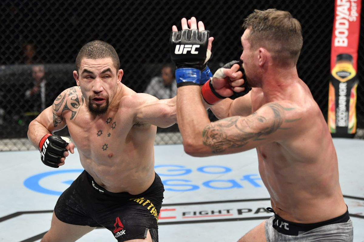 Robert Whittaker of New Zealand punches Darren Till of England in their middleweight fight during the UFC Fight Night event inside Flash Forum on UFC Fight Island on July 26, 2020 in Yas Island, Abu Dhabi, United Arab Emirates.
