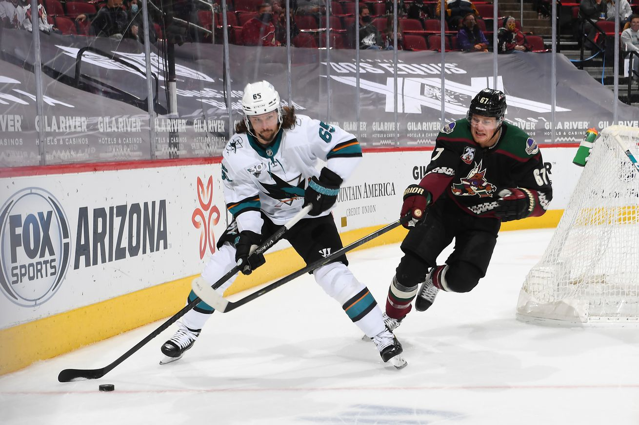 Erik Karlsson #65 of the San Jose Sharks skates with the puck while being defended by Lawson Crouse #67 of the Arizona Coyotes at Gila River Arena on March 26, 2021 in Glendale, Arizona.