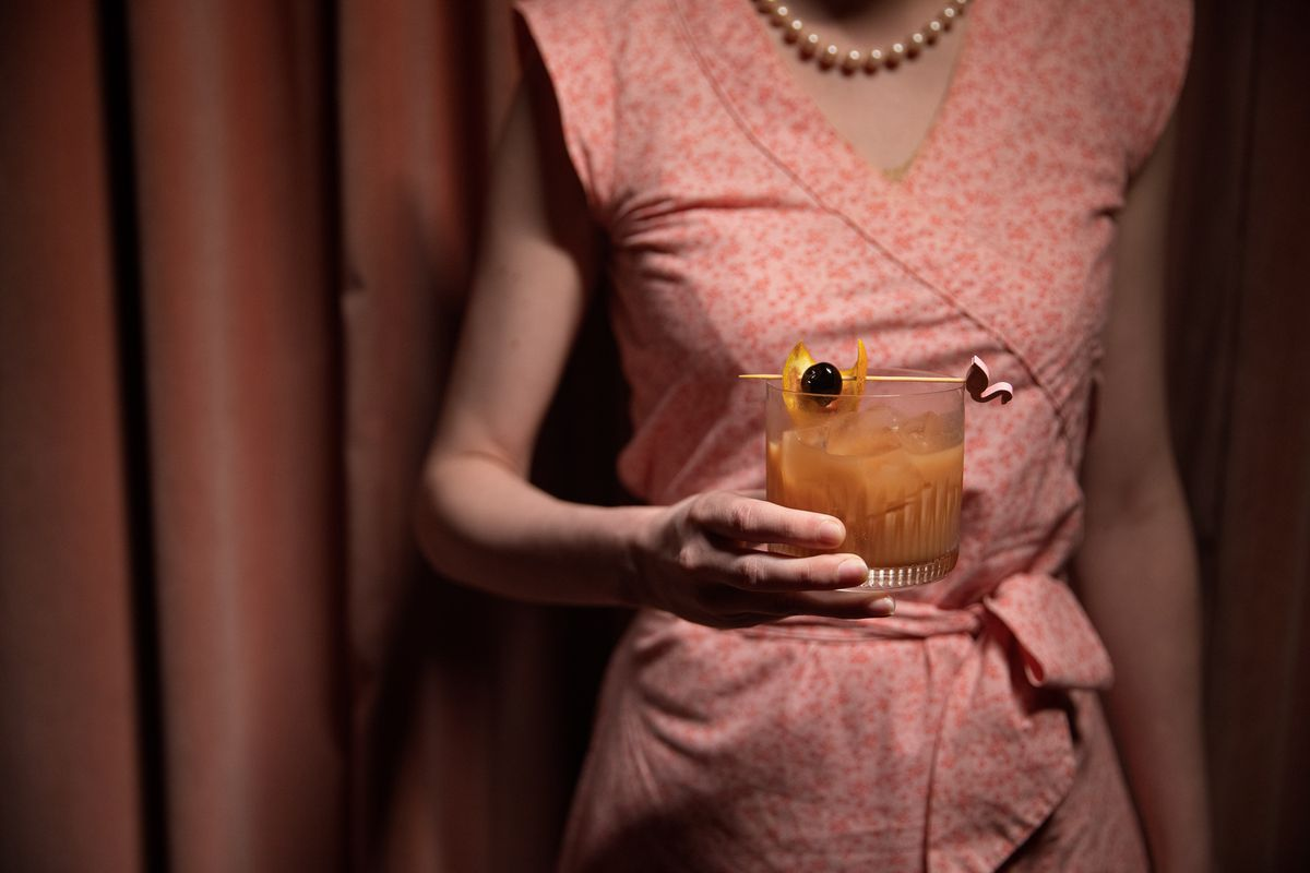 a woman in a pink dress holding an opaque pink cocktail with a cherry and orange slice skewered on a flamingo toothpick