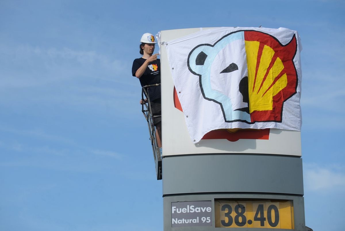 A Greenpeace activist covers the logo of the Shell oil company to protest on May 10, 2012. (Michael Cizek/AFP/Getty Images)