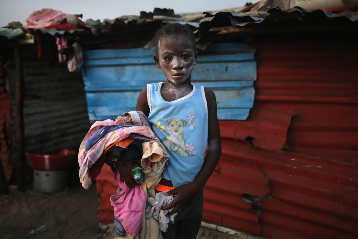A girl collects her family's laundry after drying it on a rooftop in the West Point township on January 31, 2015 in Monrovia, Liberia. Life has been disrupted by Ebola for many Liberians.