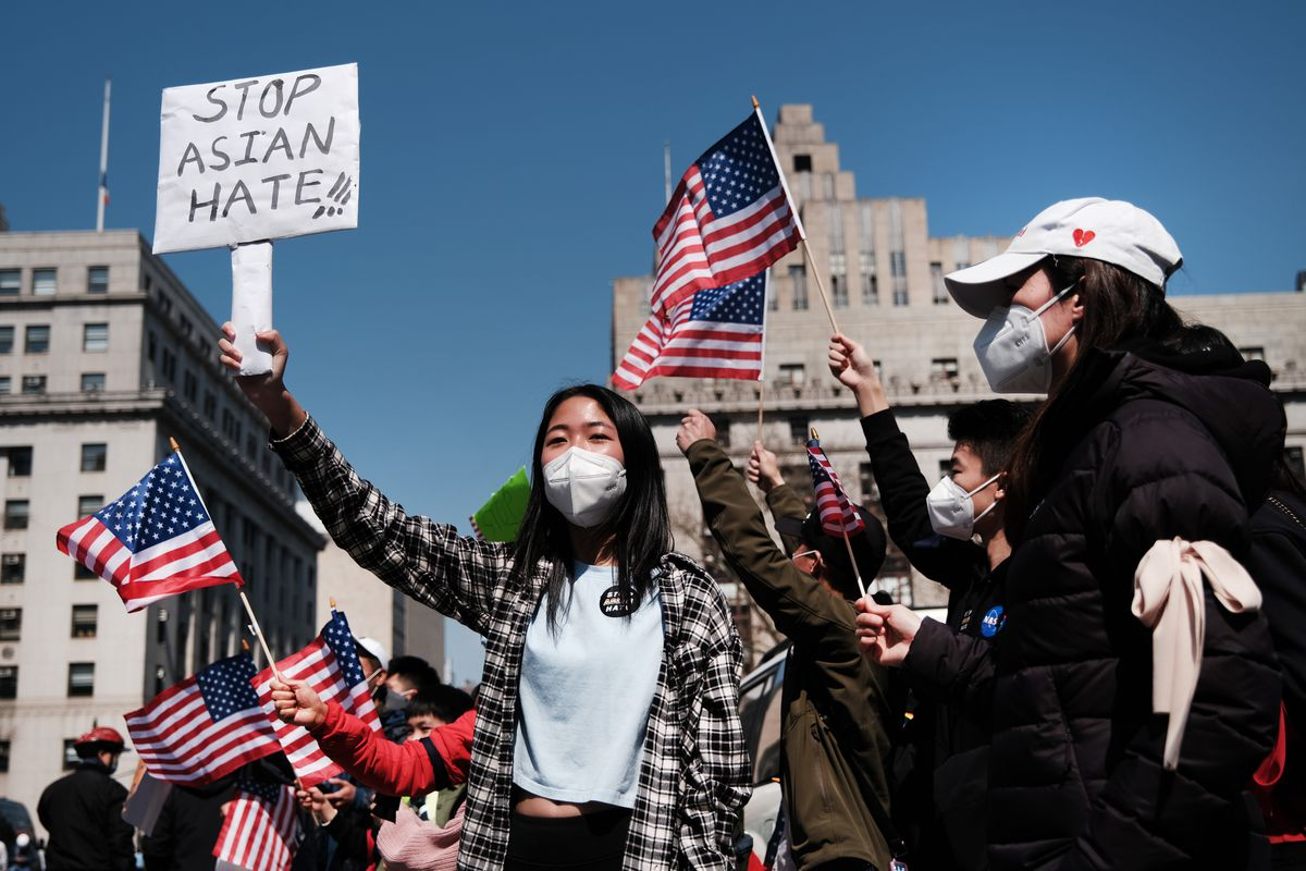 """A group of protesters hold signs, one reading """"Stop Asian Hate,"""" and wave American flags, a city skyline in the background."""