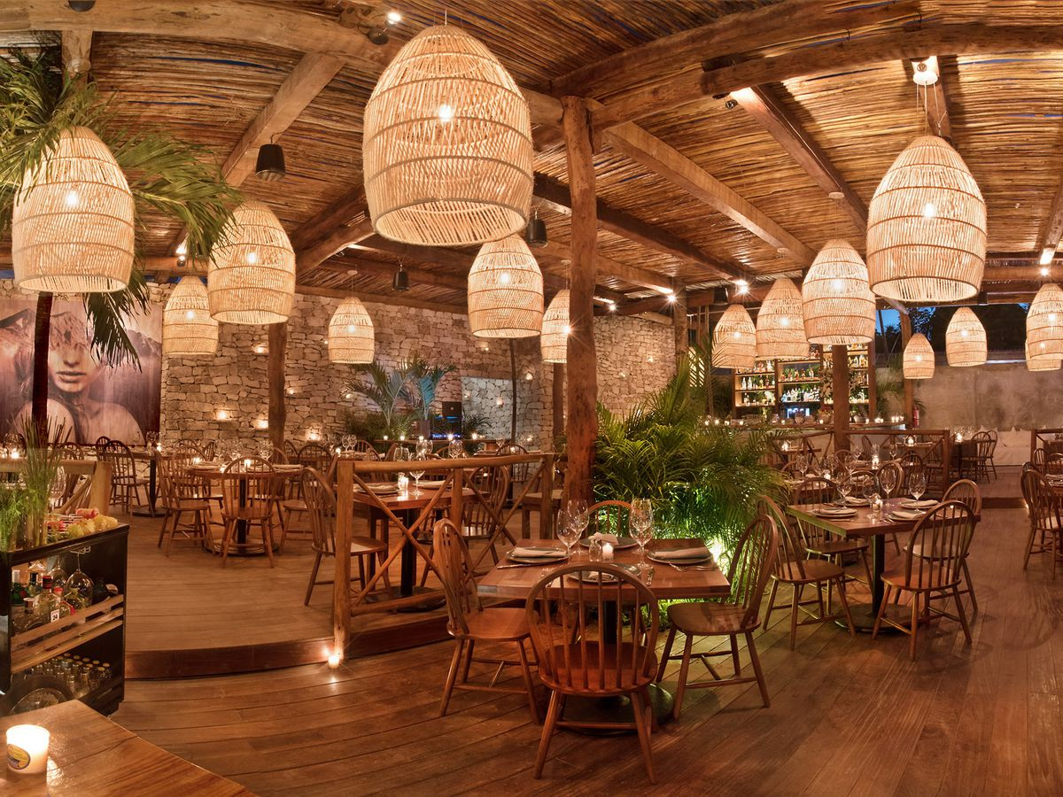 A large empty dining room covered in natural wood with a stone wall in the back, large pop-arty decorations, hanging woven lanterns, and tables set for dinner