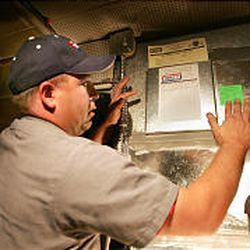 Lance Tanner applies green sticker certifying that furnace can safely burn new mixture of natural gas.