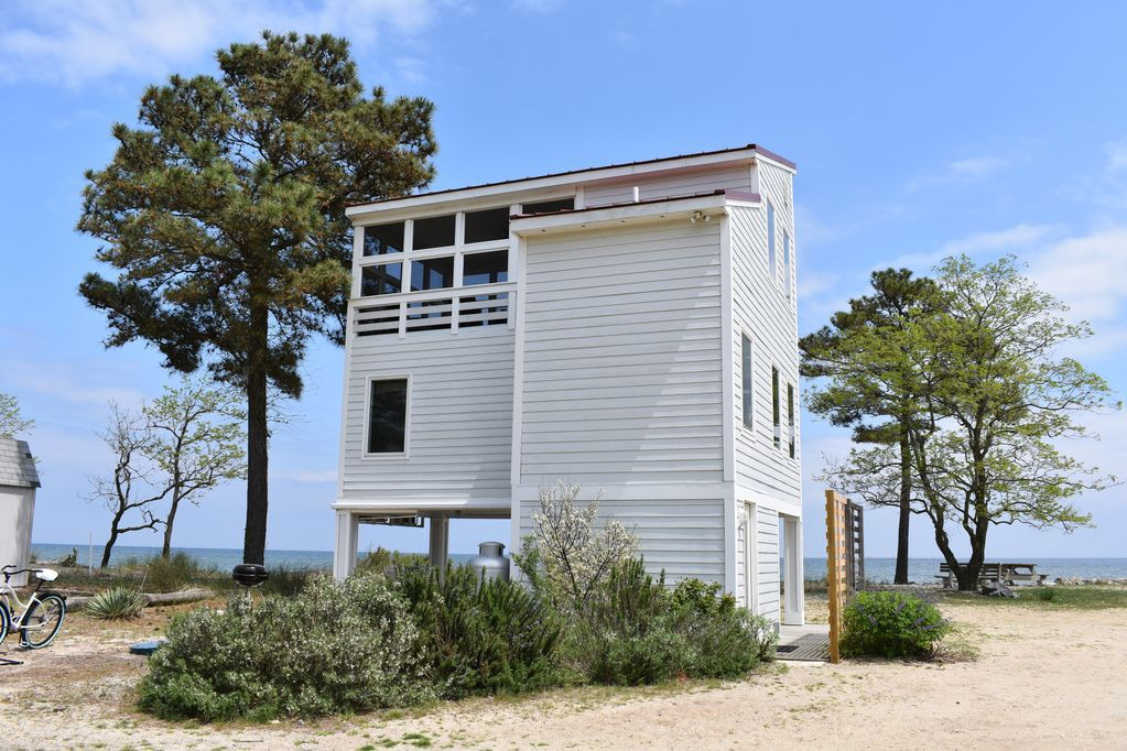 A three-story, beachfront cabin in St. Inigoes, Maryland, surrounded by bushes and trees.