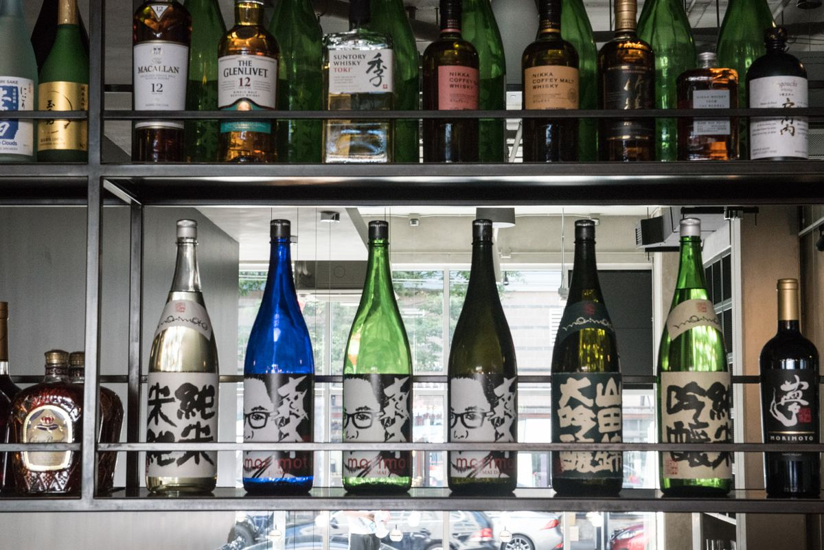 A view of the bar, with a row of Japanese whisky on top and a row of sake on the bottom, with chef Morimoto's face displayed on the labels.